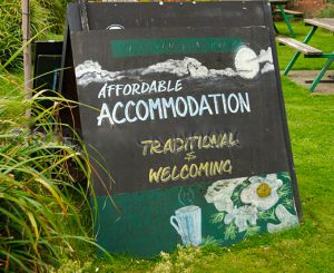 sign-outside-the-winston-hotel-advertising-affordable-accommodation-crpgj8